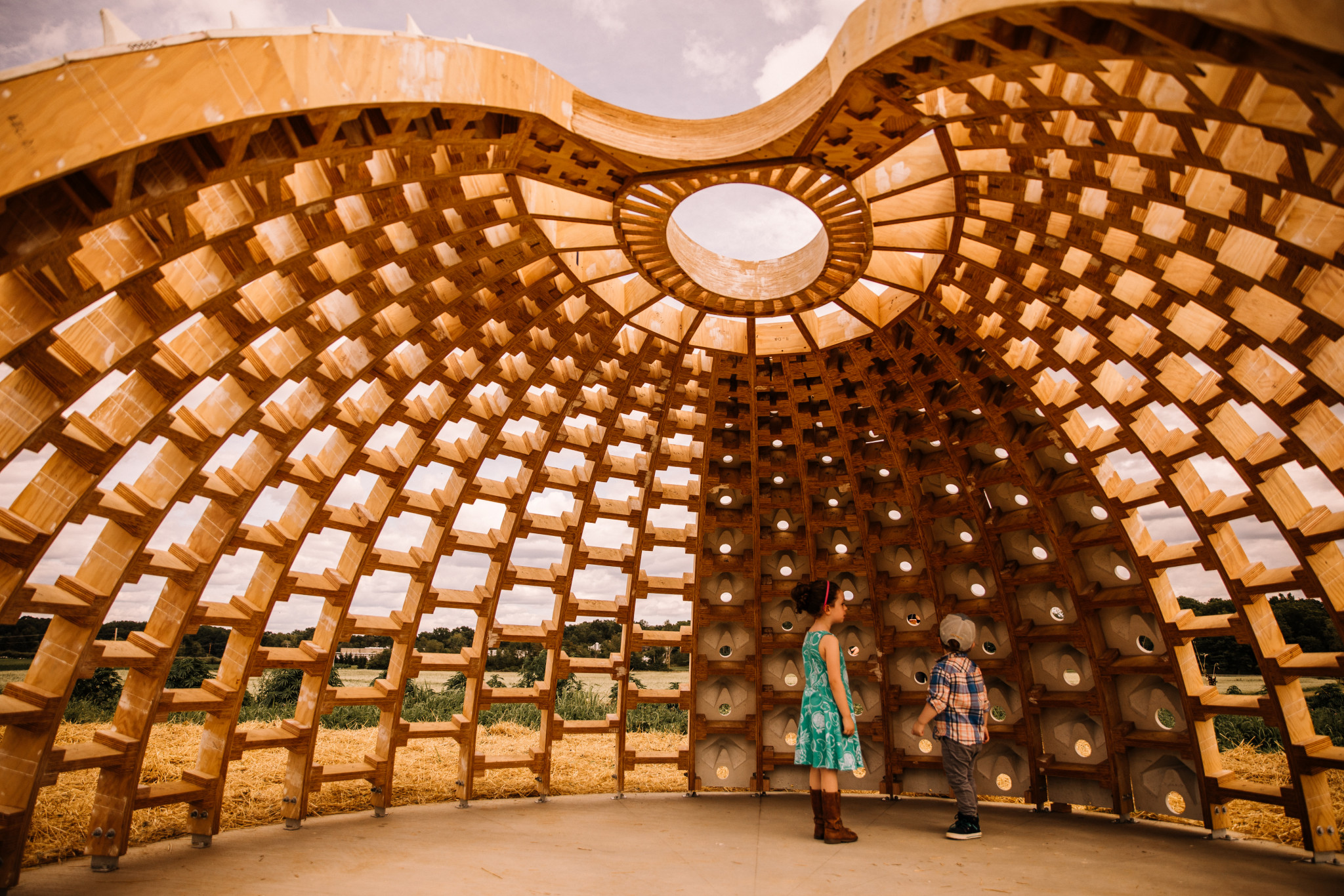 Children stand within a dome in construction with a honeycomb pattern
