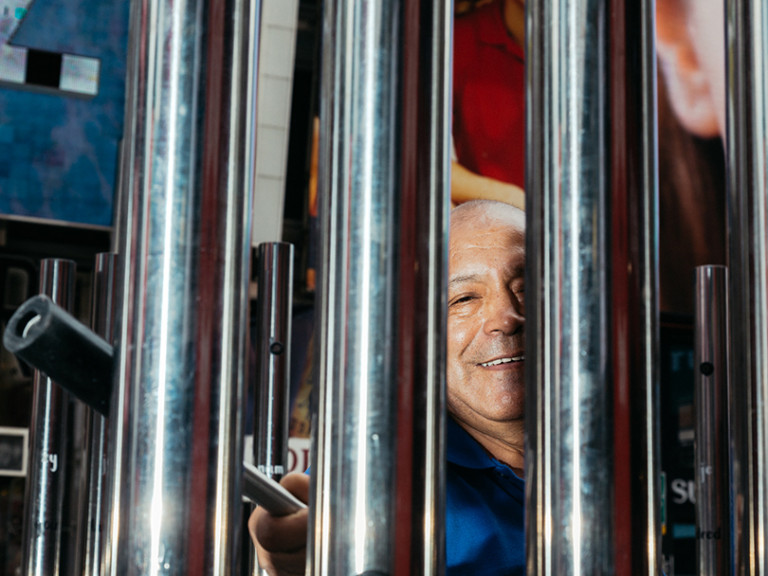 picture of a man behind hollow metal bars, he hits the bars to make a sound