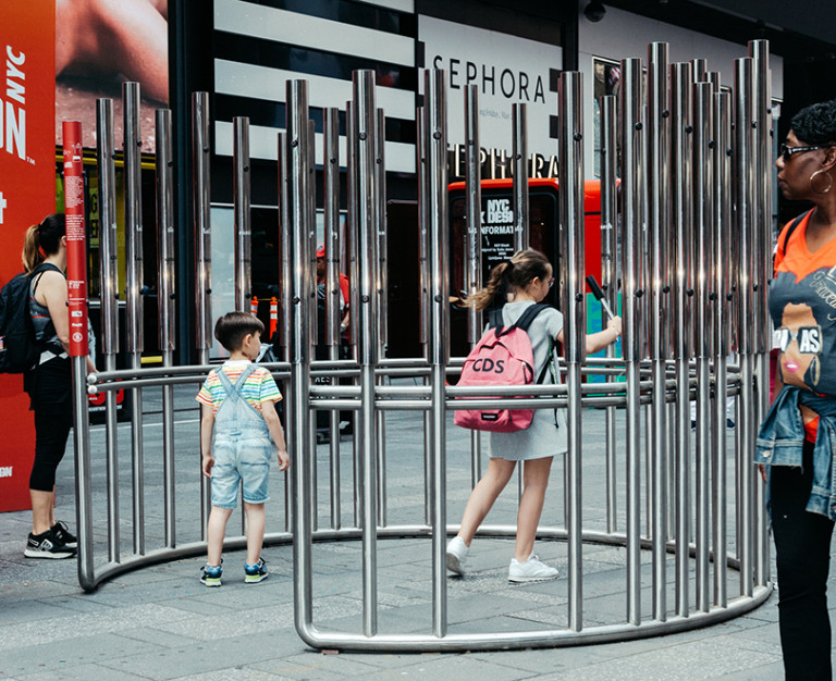 picture of children within the structure playing with the metal bars to make sounds