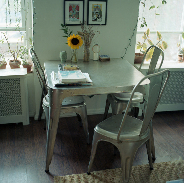Picture of a table with three chairs, a sunflower and books on top.