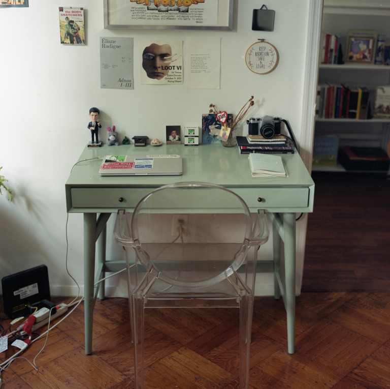 Picture of a green table with a laptop accompanied by a transparent chair