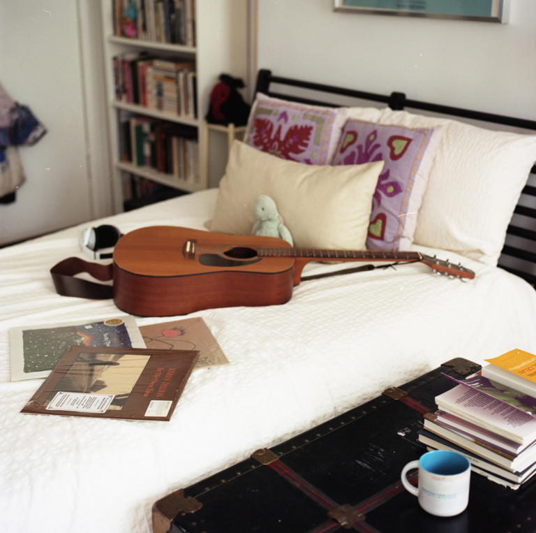 Picture of a guitar on a bed accompanied with books