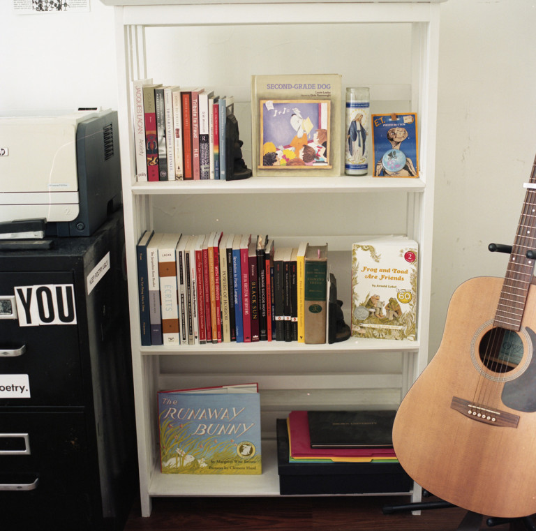 Picture of a white bookshelf and guitar
