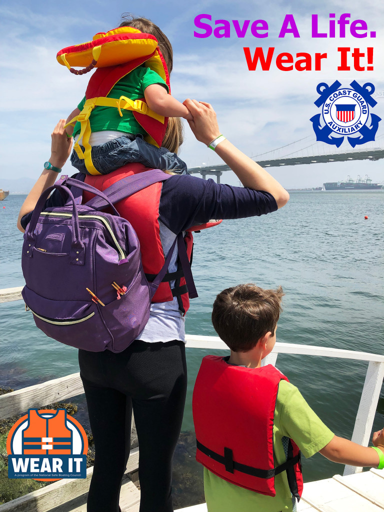 Shown from behind, an adult with a small child on their shoulders and an older child to their right, all wearing life vests, gazes out at open water, and overlaying messaging encourages the use of floatation vests
