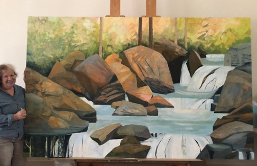 An artist stands next to a large painting of a gray-blue stream flowing through and over brown and dark gray boulders