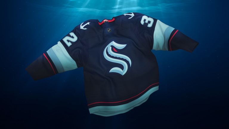 A dark-blue hockey jersey with a large S in gothic typeface on its front and white anchors on its shoulders floats underwater with thin beams of light from the surface