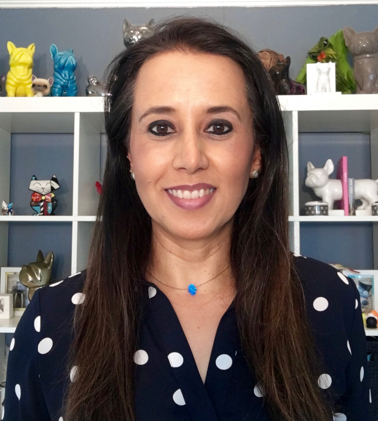 Headshot of Graciella Carillo, with long dark brown hair, brown eyes, and black-and-white polka-dot shirt against a bookcase full of whimsical sculptures of cats and dogs