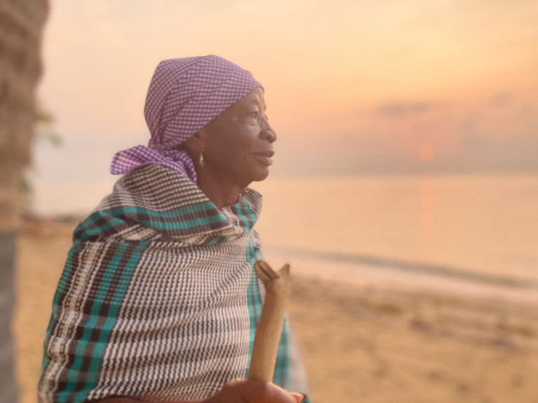 A subtly smiling dark-skinned woman with purple-and-white checked headscarf and black-and-green checked garment gazes out at the ocean illuminated in golden light