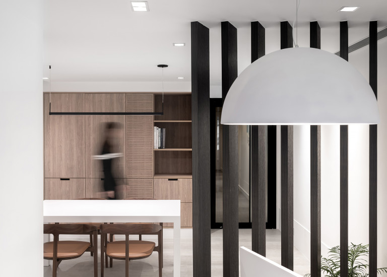 Small office area with wall of built-in wood storage cabinets, and a series of angled floor-to-ceiling wood beams dividing the room but allowing light through
