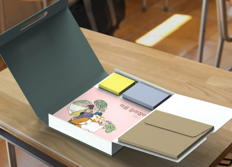 A box with a green lid with a sticky notes of yellow and blue inside, alongside a pink journal with Korean writing on it