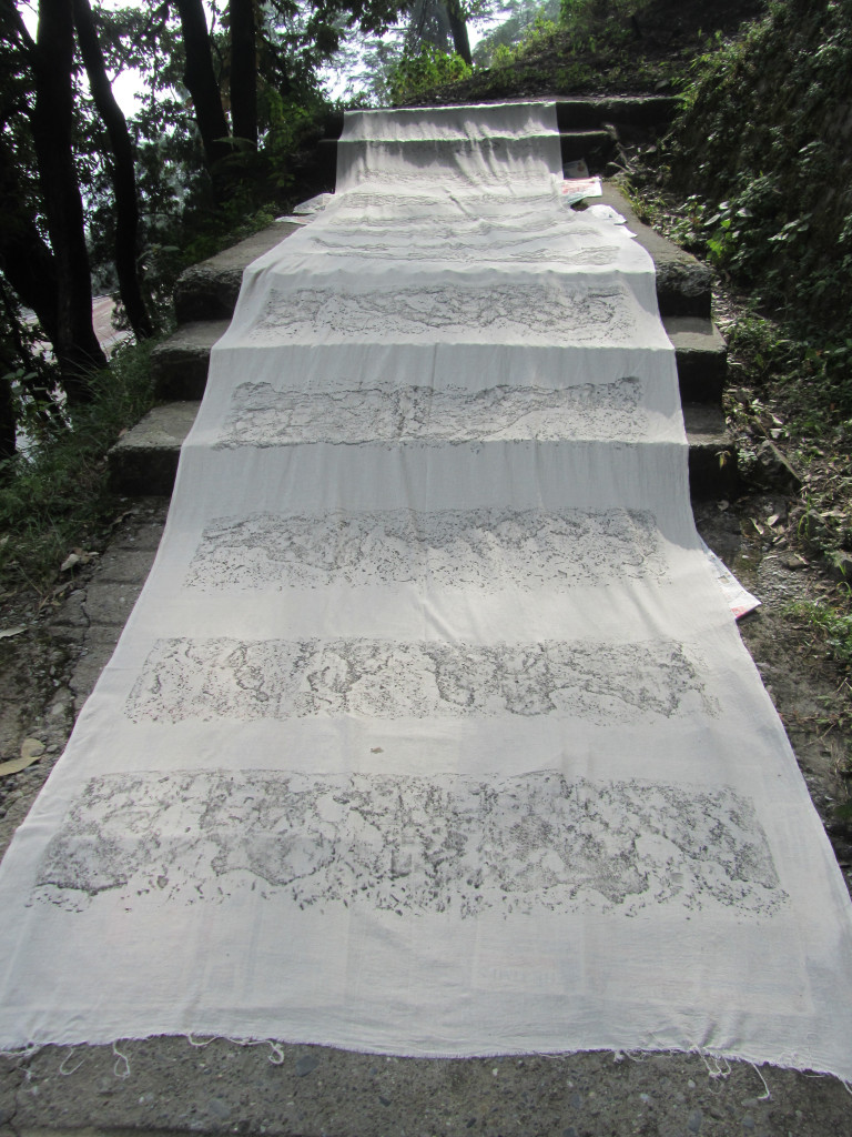 A long swath of white fabric lays on a footpath with steps, and gray markings on the fabric describe the ground surface beneath