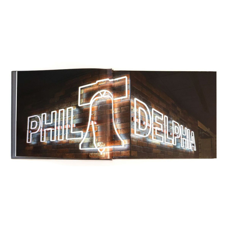 Book open to a spread showing the word Philadelphia shaped out of neon lights in block letters, with a silhouette of the Liberty Bell standing in for the first letter A, against a brick backdrop