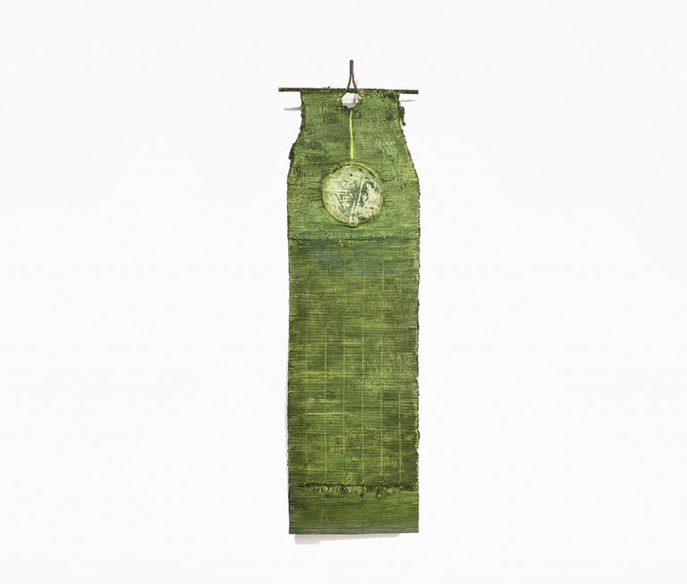 A flat, hanging sculpture made of woven paper colored green with a white circle near the top, hung from a thin brown rod