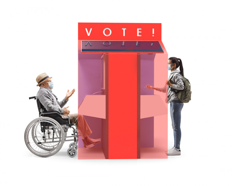 A person on a wheelchair and a standing person, voting on the separate ends of the voting booth.