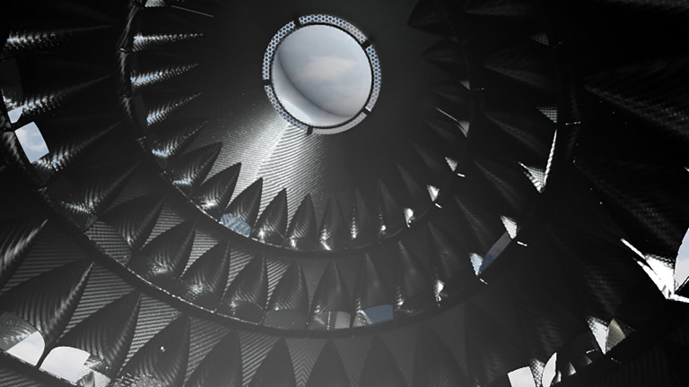 Interior of the black, ridged walls of a conical structure rising into a circular skylight with view of wintry gray-blue sky and clouds