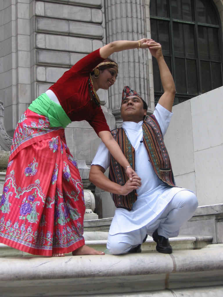 Dancer in a red skirt with purple and green flourishes, a deep red top, and golden headband arches over a second, kneeling dancer in white with a patterned vest perched on a marble step