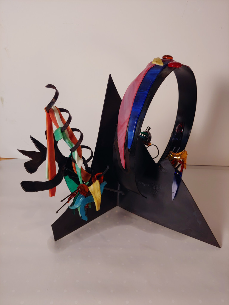 An assemblage of geometric shapes and curls and waves of metal and glass colored black, pink, orange, green, yellow, and blue
