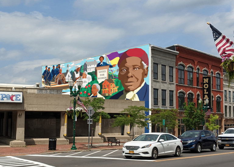 A painted mural depicting Harriet Tubman on the end facade of a block of townhouses on a tree-lined street