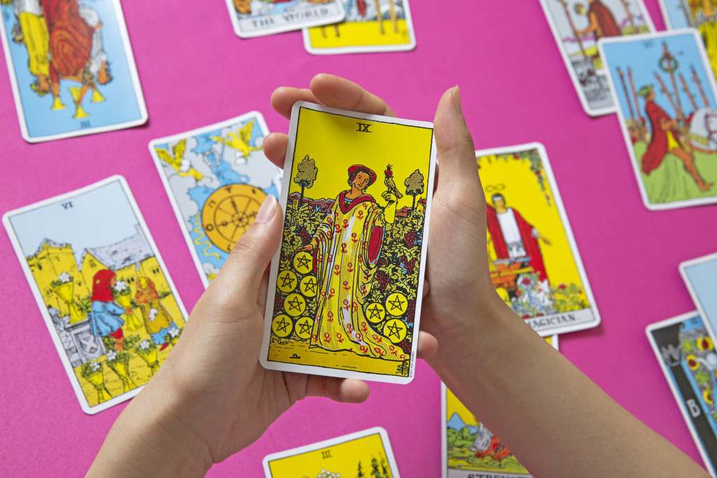 Hand holds tarot card depicting nine of pentacles, with illustration of figure in yellow gown with bird perched on their hand