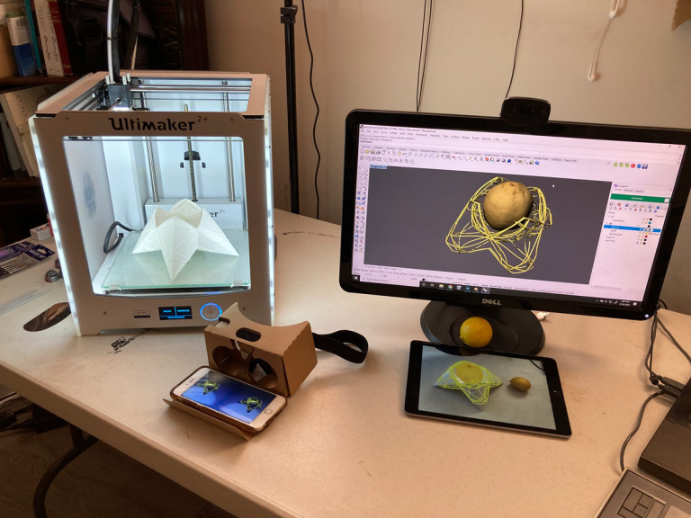 Desk with 3-D printer, augmented reality smartphone display, screens showing multiple views of a design object