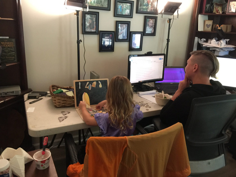 Architect Michele Gorman and young daughter sit side by side working in the architect's studio