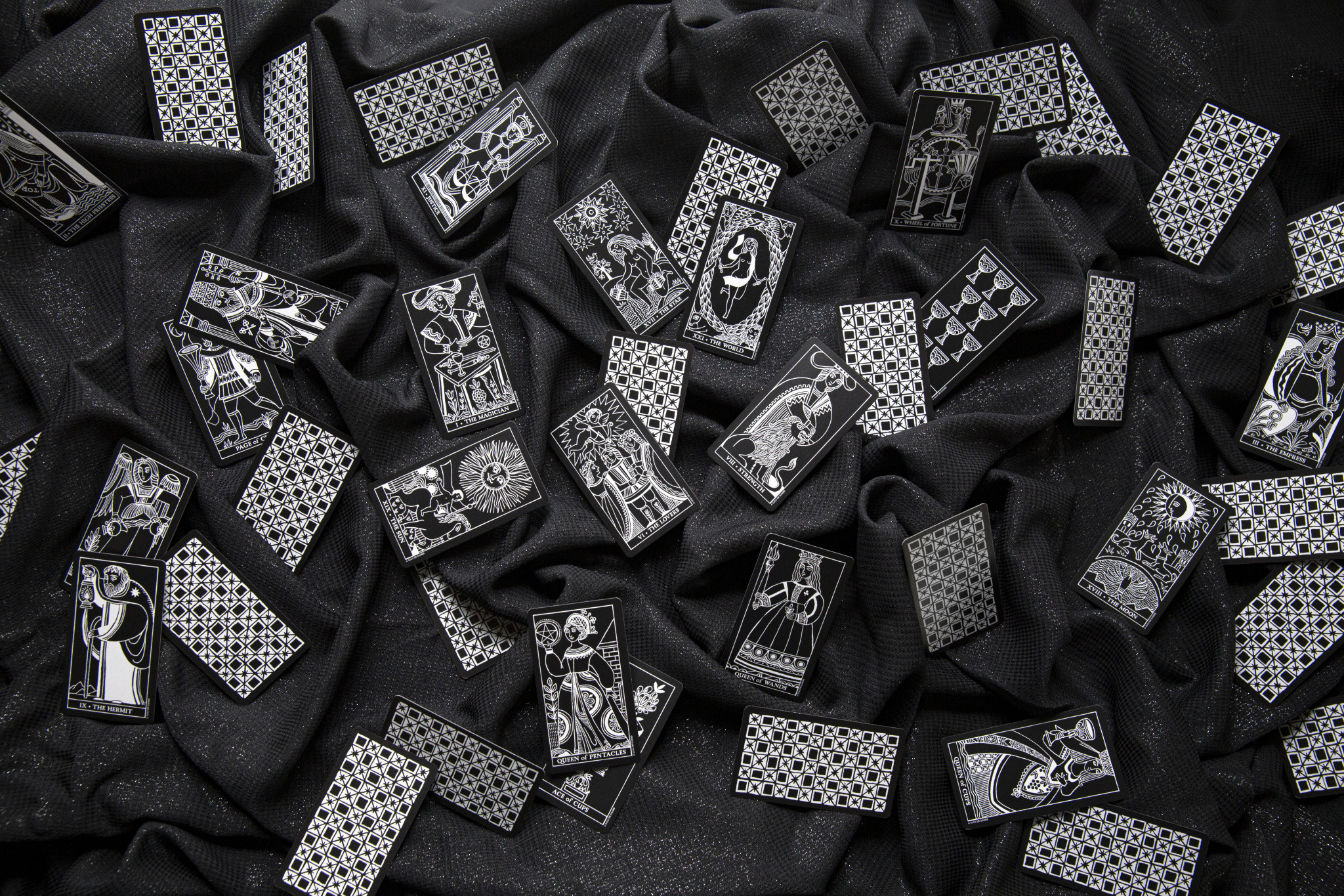 Black and white tarot cards spread across a glittery black cloth