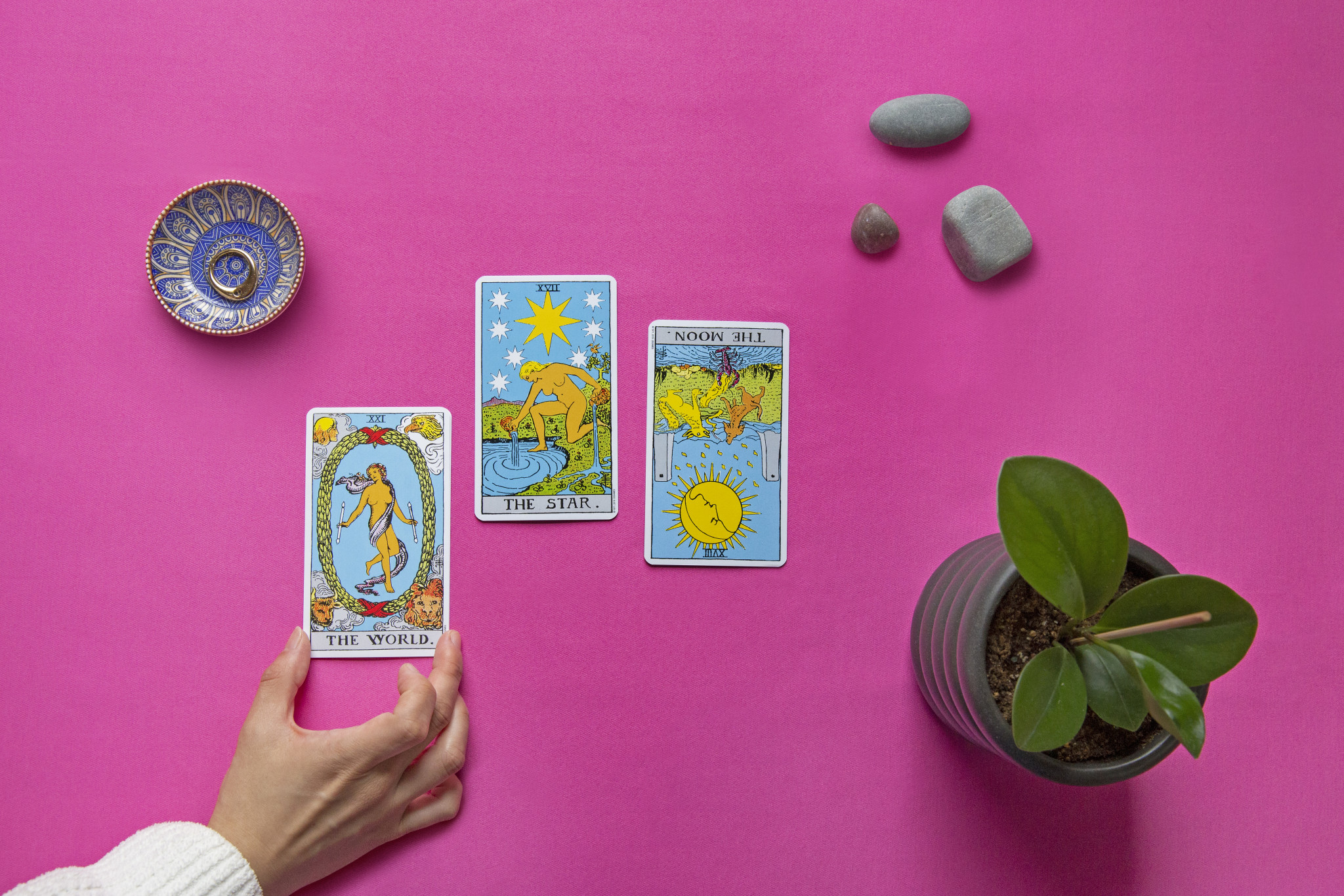A hand touches one of three cards in a tarot spread, featuring the world, the star, and the moon