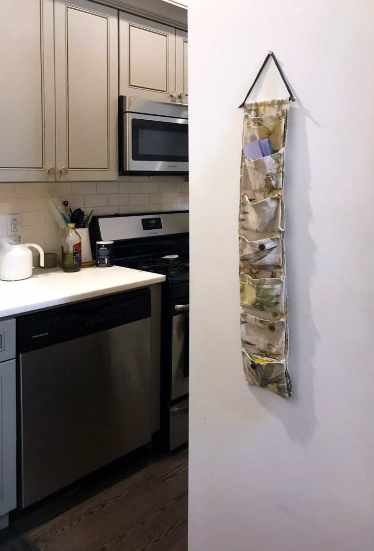 picture of a kitchen with a hanging cloth organizer