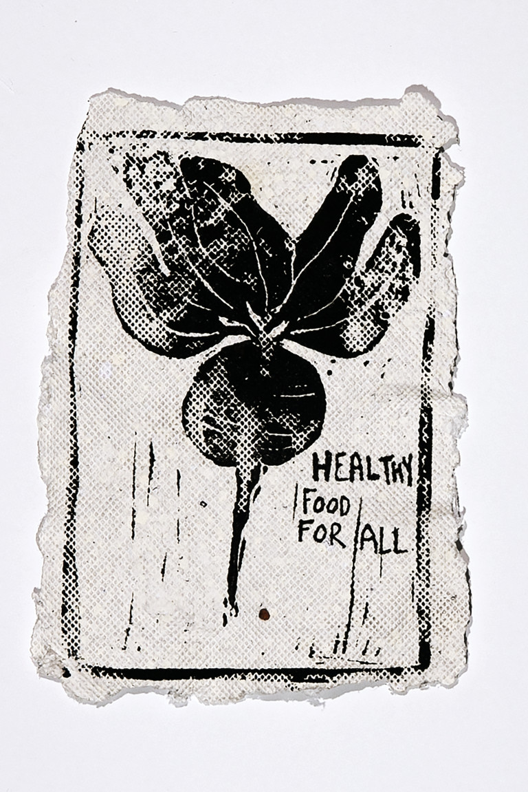 """Rough-edged paper with black-ink print of radish, with message """"healthy food for all"""""""
