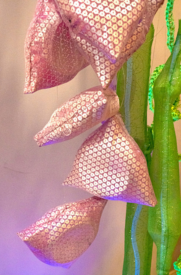 Triangular pink sequinned pouches cascade down cylindrical tubes made of green glittering organza