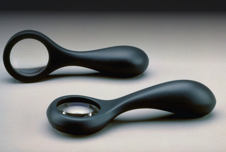 Two views of a black magnifying glass with soft, curved edges, propped on its side and lying on its back side