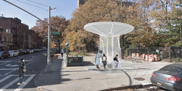 People wait on benches under the canopy of a circular structure outside the G subway station at Classon Avenue in Brooklyn