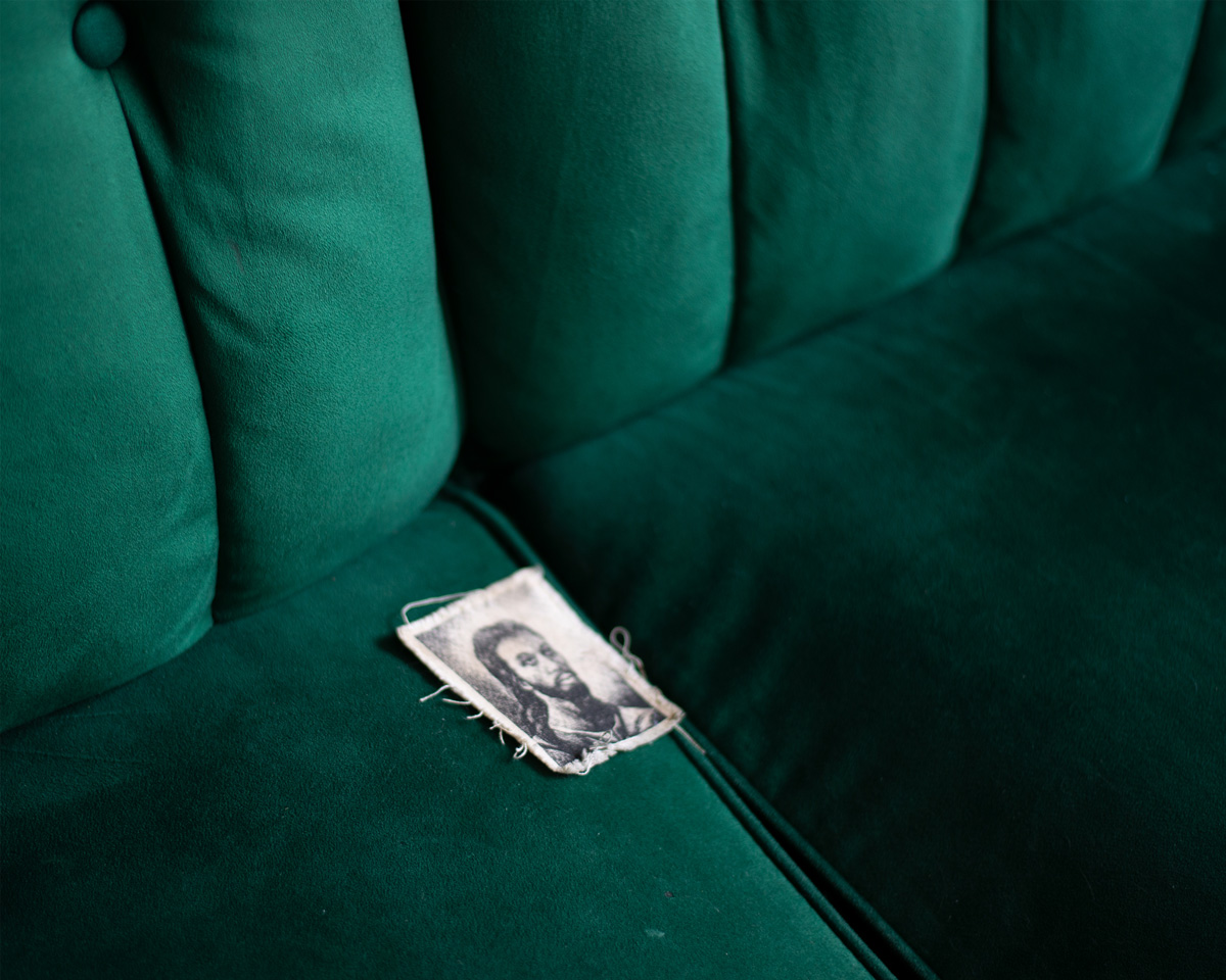 Picture of man with long dark hair and beard on a green velvet seat.