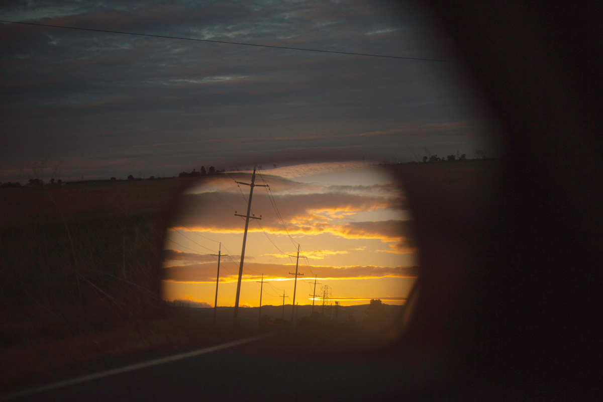 Picture of a reflection of a car side mirror of a sunset