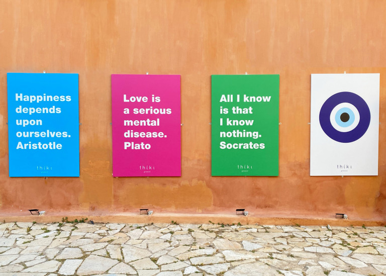 Four signs hang on a clay-colored exterior wall, with quotes from Aristotle, Socrates, and Plato and an illustration of the evil eye