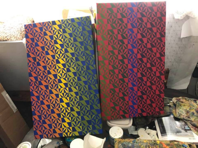 Two rectangular canvases painted with a checkered square-and-triangle pattern and gradient background color that shifts from red to yellow to blue and green to black