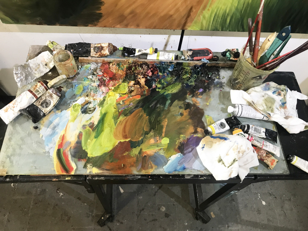 A tabletop with paints of many colors