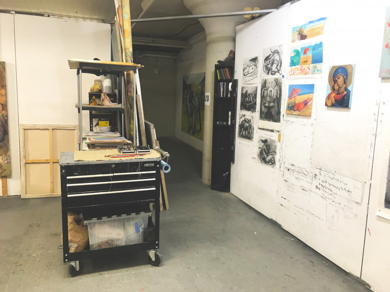 Interior of an artist's studio with work cart and paintings on a wall