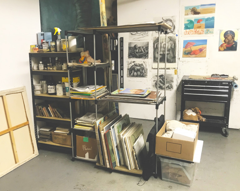 Interior of an artist's studio with shelves and paintings on a wall