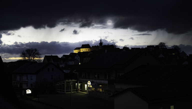 A cluster of houses and scattered bare-limbed trees on a small hillside beneath a dimly lit sky and dark clouds