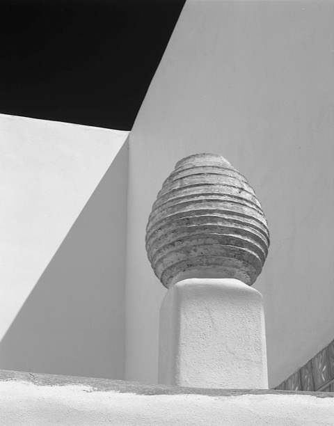 Black-and-white photo of a round, ridged vessel placed before angled walls of a building that cast sharp shadows