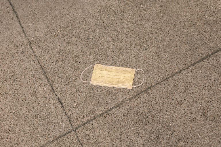 Picture of a yellow face mask on a concrete floor