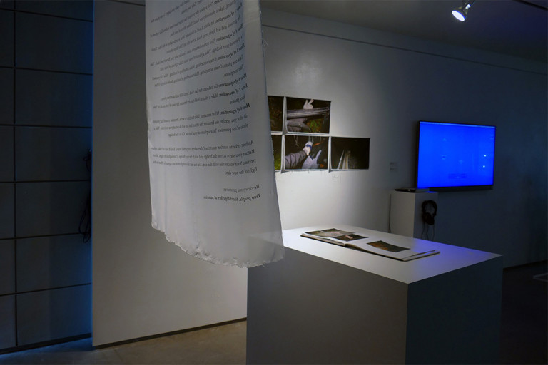 A script in a room with a few black paintings, an island countertop and a tv screen in blue.