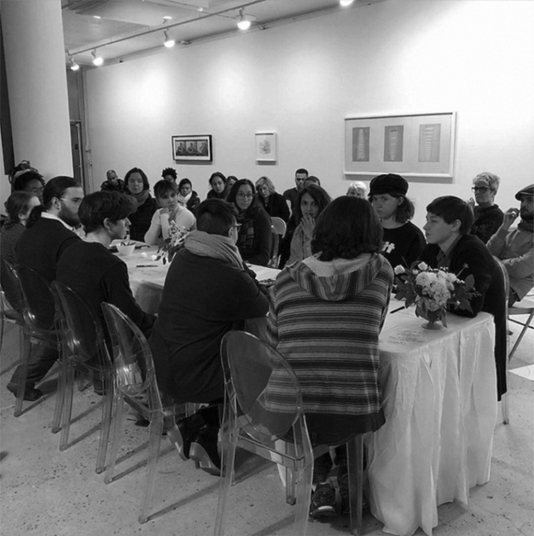 Students and faculty sit around a table in DeKalb Gallery