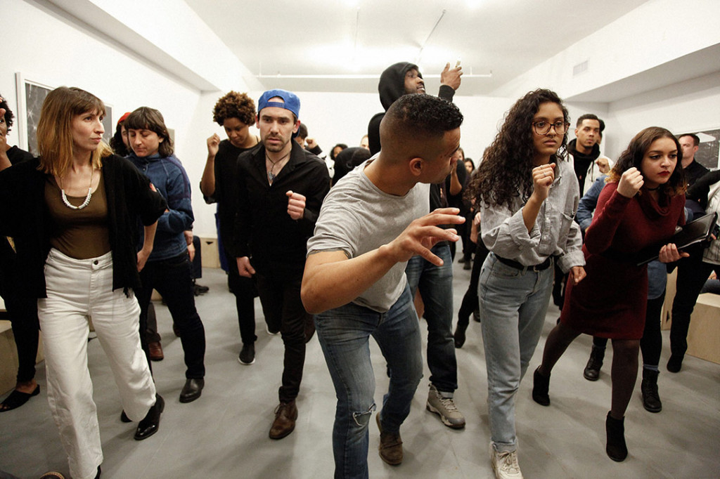 People walk in unison in a gallery space