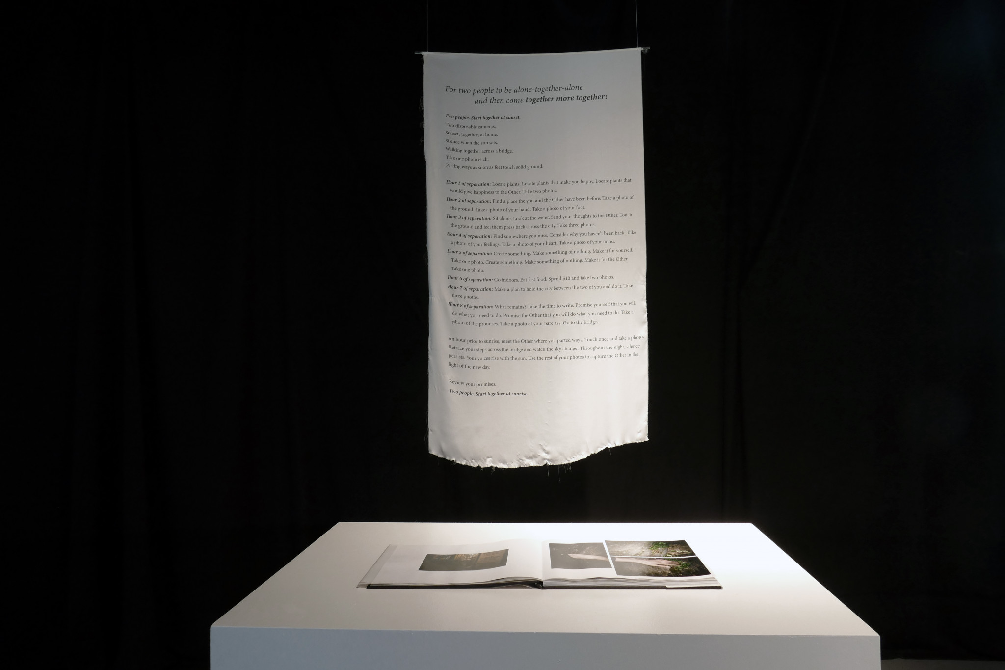 White scroll with text hangs above a white table with open photo book