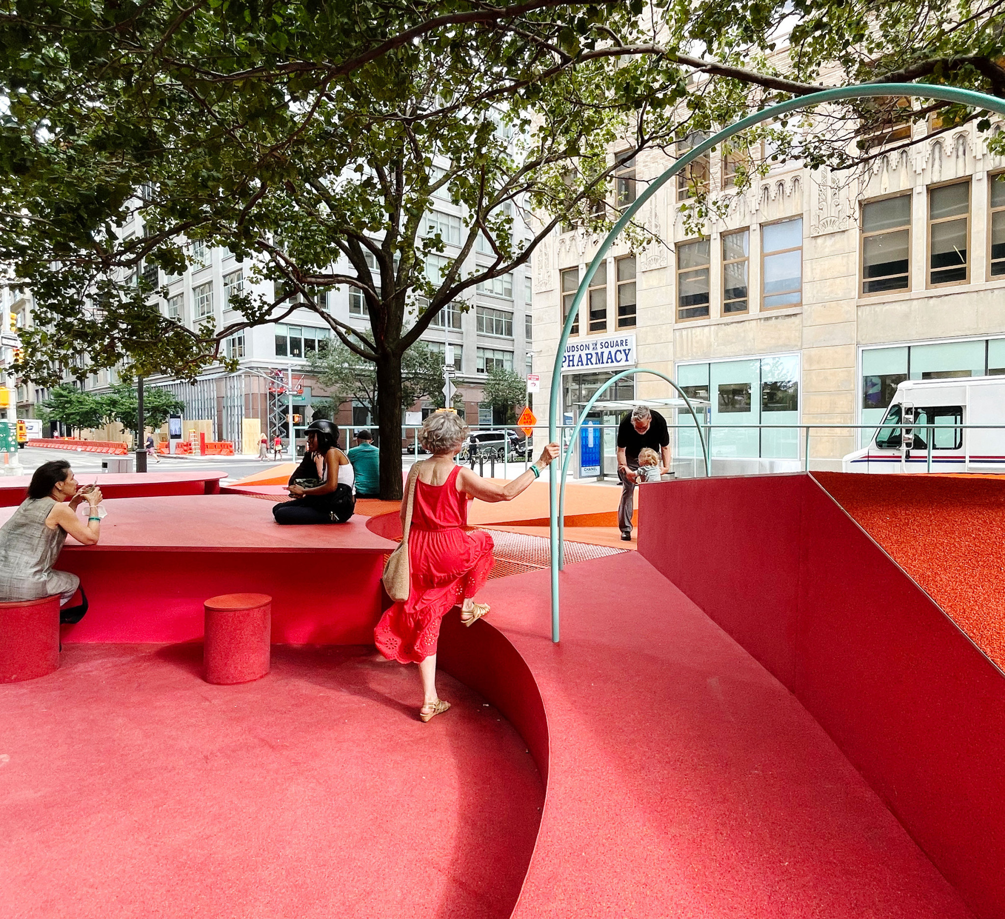 People move around a red interactive street installation