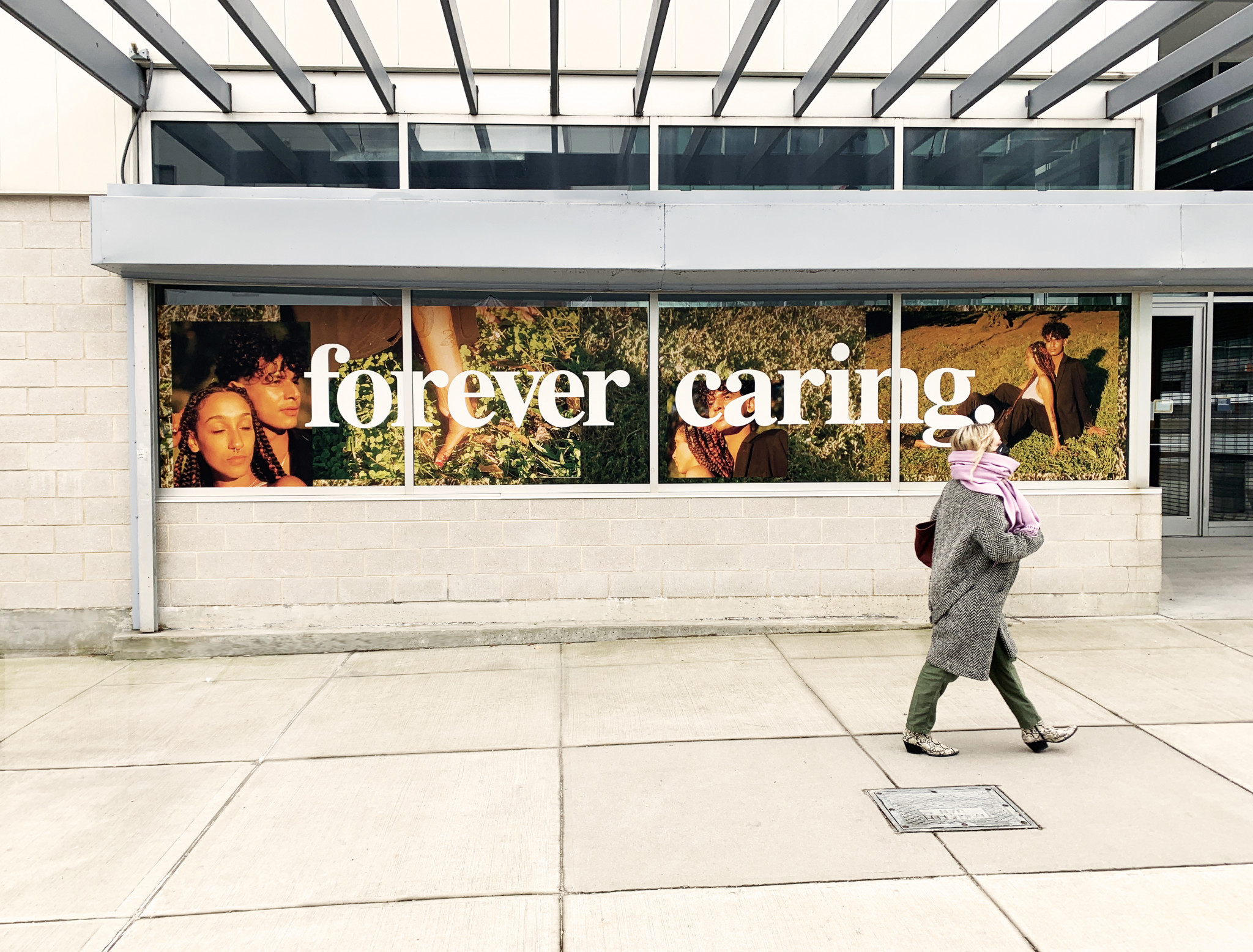 A person walks on the sidewalk in front of windows displaying images of a couple and the words forever caring.